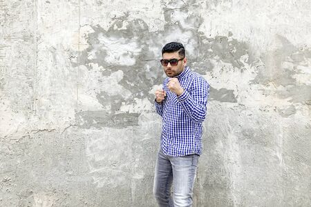 Portrait of angry handsome bearded young man in checkered blue shirt and sunglasses standing against concrete gray wall. looking at camera with serious face and ready to punching in boxing pose.