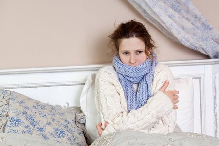 Sad alone young woman in white sweater and blue scarf feeling cold sick and resting home in bed. indoor studio shot.