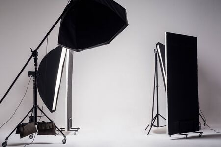 Professional photo studio with light setup included octagon softbox on boom, strip soft box and reflector on light gray background. indoor studio shot.