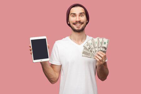 Portret szczęśliwy przystojny brodaty młody hipster mężczyzna w białej koszuli i dorywczo kapelusz stojący, trzymając tablet z pustym ekranem i zielone pudełko. Wewnątrz, na białym tle, studio strzał, różowe tło