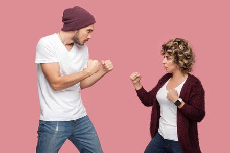 Side view portrait of upset angry couple of friends in casual style standing, disassembly and showing fists to each other, have conflict. Isolated, indoor, studio shot, pink background 写真素材