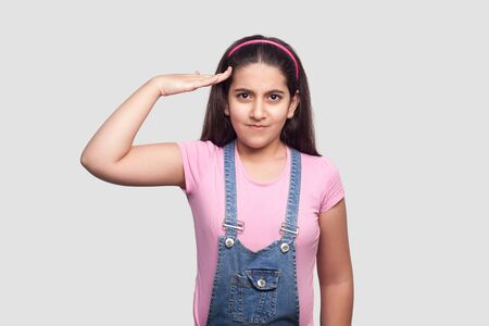 Yes sir. Portrait of serious brunette young girl in pink t-shirt and blue overalls standing with salute gesture and looking at camera attentive. indoor studio shot, isolated on light gray background. Stock Photo
