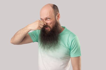 Bad smell. Portrait of confused middle aged bald man with long beard in light green t-shirt standing, blocking his nose and looking at camera. indoor studio shot, isolated on grey background. Zdjęcie Seryjne