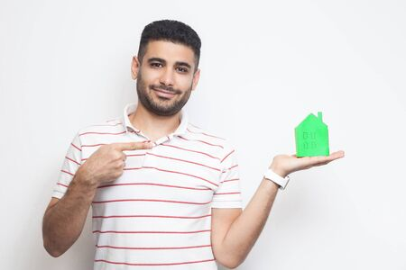 Want you own home? Happy young realtor man in t-shirt holding green paper small house and propose you to planning new home to buy. Indoor, isolated, studio shot, copy space, white background