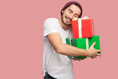 Portrait of happy satisfied handsome bearded young hipster man in white shirt and casual hat standing and holding two present bo and hugging it. Indoor, isolated, studio shot, pink background