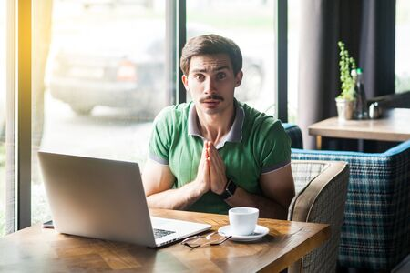 Please forgive me or help! Young worry businessman in green t-shirt sitting and looking at camera and pleading to help or forgive. business problem concept. indoor shot near big window at daytime. Stock fotó