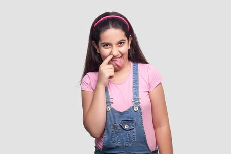 Portrait of funny brunette young girl in pink t-shirt and blue denim overalls standing, tounge out, finger in nose and drilling, looking at camera. indoor studio shot isolated on light gray background Banco de Imagens