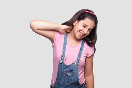 Neck pain. Portrait of sad brunette young girl in pink t-shirt and blue overalls standing and holding her painful neck and feeling bad. indoor studio shot, isolated on light gray background.