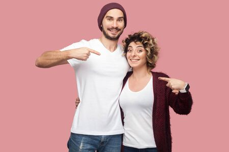 Funny couple of friends in casual style standing, hugging and pointing fingers to each other, looking at camera with happiness and toothy smile. Isolated, indoor, studio shot, pink background