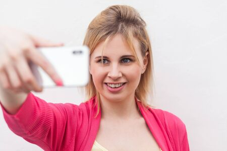 Closeup portrait of happy attractive blogger woman in pink blouse standing, holding phone and making selfie and toothy smile. indoor, studio shot, isolated on white background
