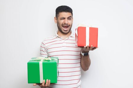 Portrait of positive attractive young adult man in t-shirt standing, holding two big gift box and winking, looking at camera. Studio shot, white background, isolated, indoor, copy space Stockfoto