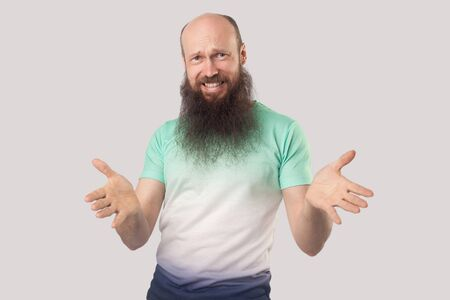 What do you need? Portrait of angry middle aged bald man with long beard in light green t-shirt standing, looking at camera with raised arms and asking. indoor studio shot isolated on grey background