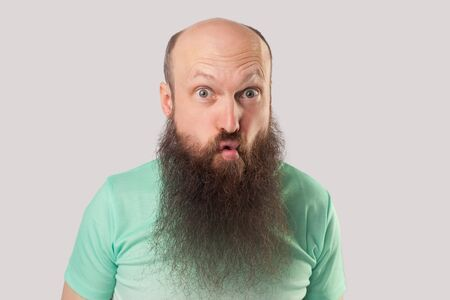 Closeup portrait of funny crazy middle aged bald man with long beard in light green t-shirt standing with big eyes and fish lips pout. indoor studio shot, isolated on grey background.