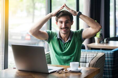 Young happy businessman in green t-shirt sitting and looking at camera with happiness and toothy smile, and home roof gesture on his head. business concept. indoor shot near big window at daytime.