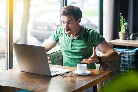 Young angry businessman in green t-shirt sitting, working, looking and screaming at laptop screen on video call. business problem concept. indoor shot near big window at daytime.