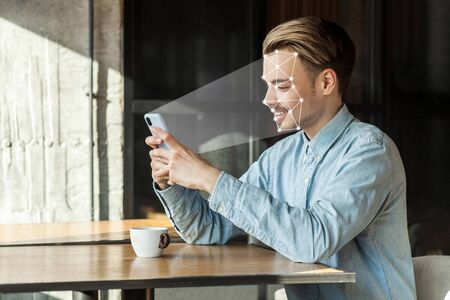 Mobile biometric identification and verification face detection concept. face ID scaning or unlocking technology. young happy man sitting and scanning face with facial recognition system on smartphone 写真素材