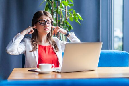 Portrait of young woman in glasses sitting, looking at her laptop screen on video call with finger closing her ears listening. indoor studio shot, cafe, office background.