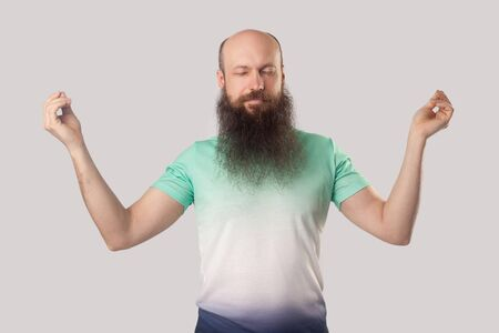 Portrait of calm relaxed middle aged bald man with long beard in light green t-shirt standing with closed eyes, raised arms and doing yoga meditation. indoor studio shot, isolated on grey background. Фото со стока