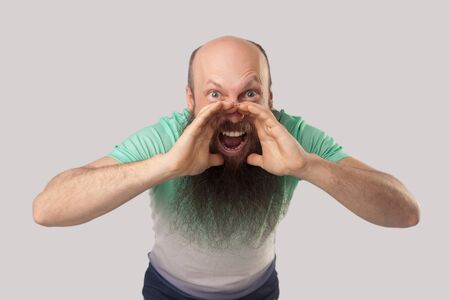 Portrait of middle aged bald man with long beard in light green t-shirt standing looking and screaming with raised arms. indoor studio shot, isolated on grey background.