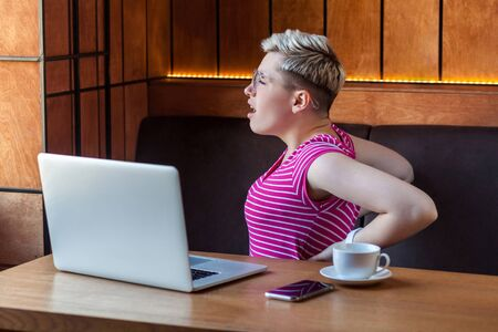 Portrait of feel tired young woman with short blonde hair in pink t-shirt and eyeglasses sitting in cafe and holding back with hand after long time sitting on computer, making massage. Indoor, health Stockfoto