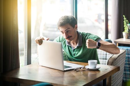 Young angry businessman in green t-shirt sitting with aggressive face and boxing fists and try to punching his laptop. 写真素材