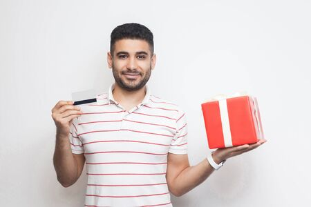 Satisfied attractive young adult man in t-shirt standing, holding big gift box and credit card with smile, online shopping, looking at camera. Studio shot, white background, isolated, indoor