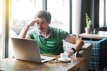 Young attentive businessman in green t-shirt sitting and working on laptop, holding hand on his forehead and looking to something. business and freelancing concept. indoor shot near window at daytime.