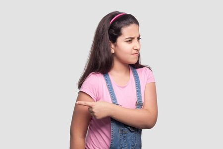 Portrait of angry beautiful brunette young girl in casual style, pink t-shirt and blue denim overalls standing and showing exit way. indoor studio shot, isolated on light gray background.