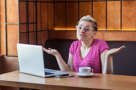 Confused young girl freelancer with blonde short hair, in pink t-shirt and eyeglasses is sitting in cafe and working on laptop with raised arms and puzzled face, looking at camera.