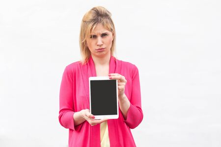 Portrait of dissatisfied beautiful young businesswoman in pink blouse standing and holding tablet empty screen and looking at camera with unhappy face. Indoor, isolated, studio shot, white background