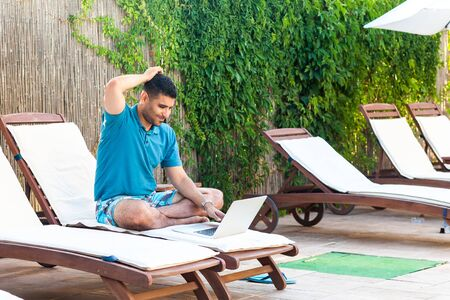 Portrait of clever handsome bearded young adult freelancer man in blue t-shirt and shorts sitting on cozy deck chair with laptop on poolside, working online and finding solution in his head. Lifestyle