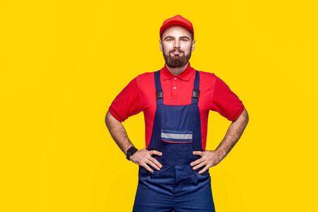 Porträt eines jungen selbstbewussten Mechanikers mit Bart in blauem Overall, rotem T-Shirt und Mütze, der mit Lächeln an der Taille steht und die Hände hält, Innen, Studioaufnahme, isoliert auf gelbem Hintergrund, Kopierraum Standard-Bild