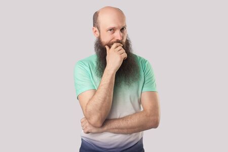 Portrait of thoughtful middle aged bald man with long beard in light green t-shirt standing and looking at camera, thinking about something. indoor studio shot, isolated on grey background.