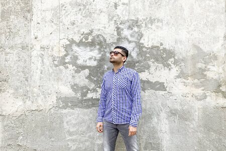 Portrait of clever genius handsome bearded young man in checkered blue shirt and sunglasses standing against concrete gray wall. looking up with serious face and thinking.