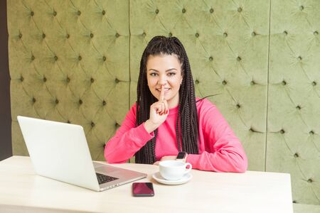 Portrait of young girl freelancer with black dreadlocks hairstyle in pink blouse sitting in cafe, making video call on laptop, lean finger on mouth showing silence, looking at camera Stock Photo