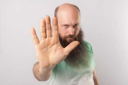 Stop it. Portrait of serious middle aged bald man with long beard in light green t-shirt standing with stop hand gesture and looking at camera. indoor studio shot, isolated on grey background. Stock Photo