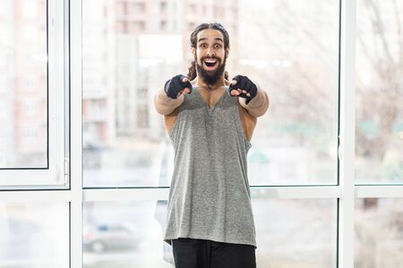 Portrait of surprised happy young adult muscular trainer man with curly long hair standing, pointing fingers to you with big eyes, looking at camera with toothy smile. Indoor, window background