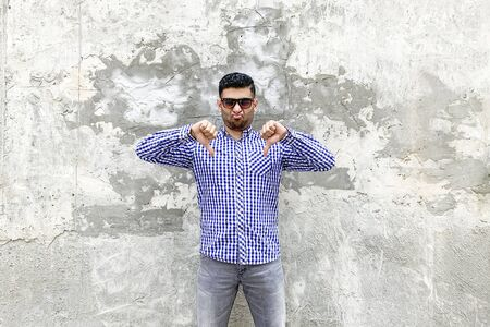 I don't like this. Portrait of dissatisfied handsome bearded young man in checkered blue shirt, sunglasses standing against concrete gray wall. showing dislike thumbs down and looking with upset face