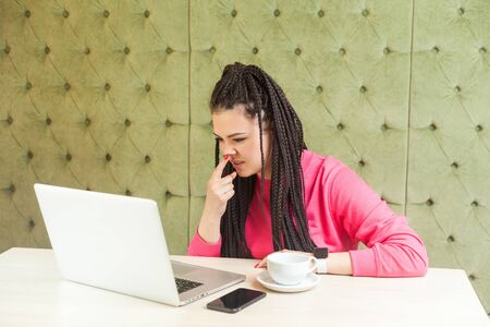 Young freelancer woman with black dreadlocks hairstyle in pink blouse is sitting and making video call on laptop, talking and pointing finger to nose to showinn lie gesture. indoor Stockfoto