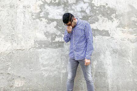 Porträt eines traurigen depressiven allein gutaussehenden bärtigen jungen Mannes in kariertem blauem Hemd und Sonnenbrille, der gegen eine graue Betonwand steht. Kopf nach unten halten und weinen.