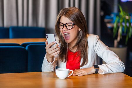 Portrait of shocked, angry beautiful stylish brunette young woman in glasses sitting and looking at her mobile smart phone and screaming with unbelievable. indoor studio shot, cafe, office background. 写真素材