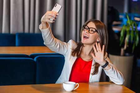 Portrait of happy joyful beautiful stylish brunette young woman in glasses sitting on video call or doing selfie with toothy smile and happiness waving hand. indoor studio shot, cafe office background