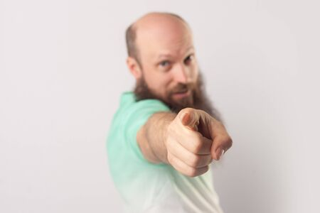 Portrait of funny middle aged bald man with long beard in light green t-shirt standing, pointing and looking at camera.