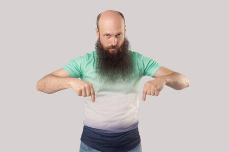Portrait of serious middle aged bald man with long beard in light green t-shirt standing, pointing down and looking and commanding. indoor studio shot, isolated on grey background Reklamní fotografie