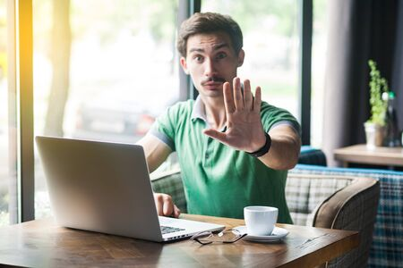 Young serious businessman in green t-shirt sitting, working on laptop, looking at camera, showing stop sign gesture. business and freelancing concept. indoor shot near window at daytime. Фото со стока