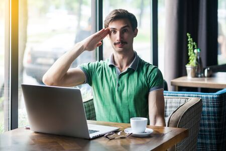 Young serious businessman in green t-shirt sitting and looking at camera with salute gesture and ready to complete the mission. business concept. indoor shot near big window at daytime.