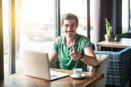 Like! Young happy businessman in green t-shirt sitting and working on laptop, looking at camera with thumbs up and toothy smile. business and freelancing concept. indoor shot near window at daytime.