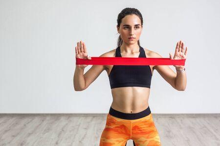 Portret młodej kobiety sportowy na sobie czarny top i pomarańczowe legginsy wykonuje ćwiczenia mięśni rąk, trening z taśmą oporową na białym tle. Siła i motywacja. Wnętrz