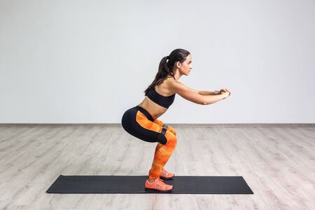 Side view portrait of young sporty healthy beautiful woman in black top and orange leggings doing squatting with elastic resistance band. Isolated, white wall, indoor, workout concept, looking away Фото со стока