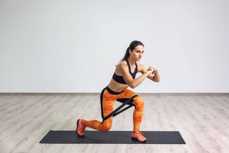 Portrait of young sporty healthy attractive woman in black top and orange leggings doing lunge with elastic latex resistance band. Isolated, white wall, indoor, workout concept, looking away